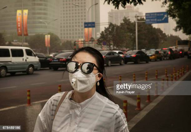 Chinese woman wears a mask to protect from particles blown in during a sandstorm as she walks in the street on May 4 2017 in Beijing China Sandstorms...
