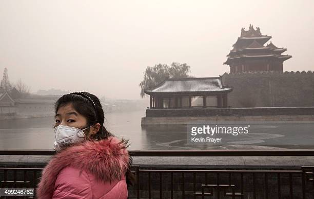 Chinese woman wears a protective mask as she walks outside the Forbidden City on a day of heavy pollution on November 30 2015 in Beijing China...