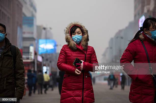 Chinese woman wears mask to protect agains pollution as she walks through a shopping area in heavy smog on December 8 2015 in Beijing China The...