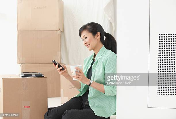 Chinese woman with boxes in new home