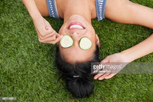Chinese woman with cucumbers on eyes laying in grass
