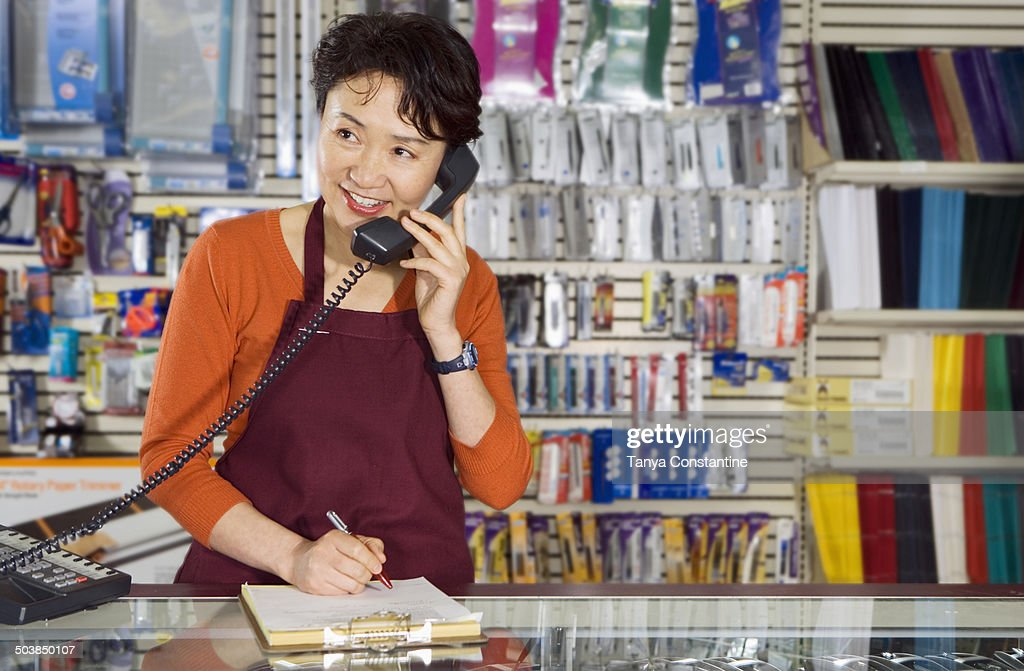 Chinese woman working in office supply store : Foto de stock