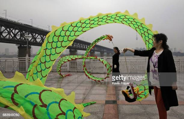 Chinese women exercise with dragons next to the Great Bridge on the Yangtze River or Chang Jiang on May 16 2017 in Wuhan Hubei province China