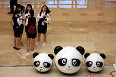 Chinese women gather near panda dolls at the venue ahead of the G20 Finance Ministers and Central Bank Governors Meeting to be held over the weekend...