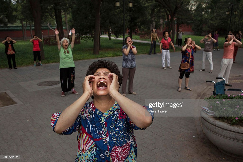 Chinese women shout as they do voice exercises at Ritan Park on June 12, 2016 in Beijing, China. Ritan, meaning 'sun altar', is among the oldest parks in Beijing, built in the early 1500s during the Ming dynasty for the emperor to make sacrifices to the sun. Less than half a kilometer square, Ritan these days is considered an oasis of green space in a sprawling city of skyscrapers, notorious air pollution, and a population of over 20 million people. Most Chinese live in small apartments with no access to gardens, leaving parks as a welcome haven for people, especially the elderly, to exercise, socialize, or enjoy a degree of privacy. The average day at Ritan is a showcase of conventional routines such as jogging, dancing, and martial arts, mixed with the assortment of odd activities -- including 'voice exercises' and back-scratching on trees -- that are known to be unique staples of Beijing park life.