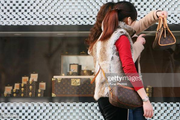 Chinese Women view the bags they bought at a Louis Vuitton flagship store on March 10 2006 in Shanghai China According to state media statistics show...