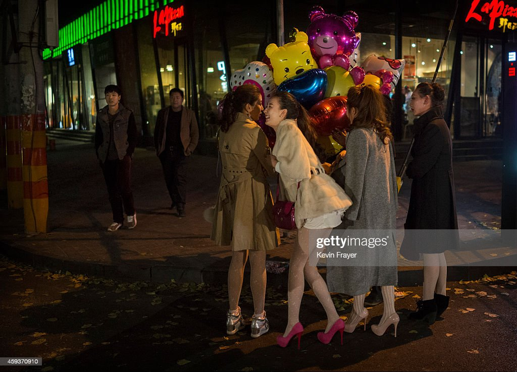 Chinese women wait to buy balloons for sale on the street in front of a bar on November 21 2014 in Hebei just outside Beijing China The Hebei...
