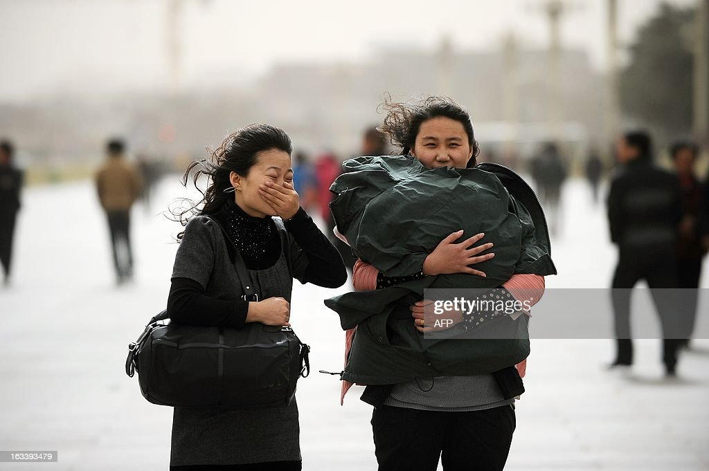 Chinese women walk in strong winds near Tiananmen Square in Beijing on March 9, 2013. Strong winds and dust storms swept the Chinese capital on March 9.