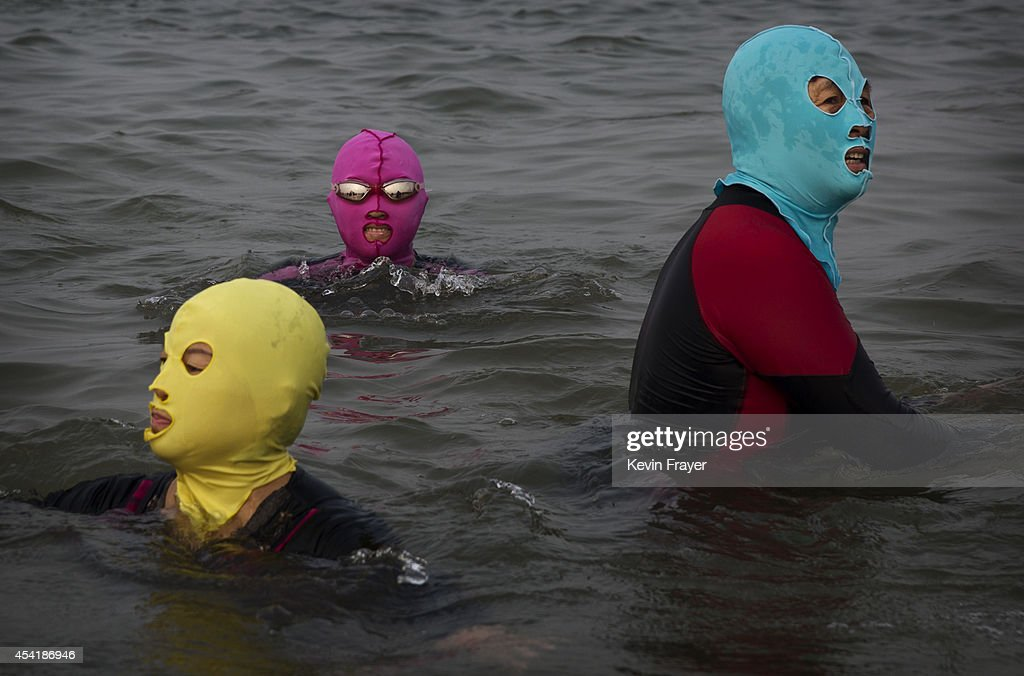 Chinese women wear facekinis as they swim on August 22 2014 on the Yellow Sea in Qingdao China The locally designed mask is worn by many local women...