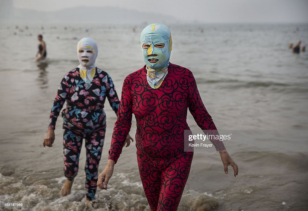 Chinese women wear face-kinis as they walk out of the water after swimming on August 22, 2014 in the Yellow Sea in Qingdao, China. The locally designed mask is worn by many local women to protect them from jellyfish stings, algae and the sun's ultraviolet rays.