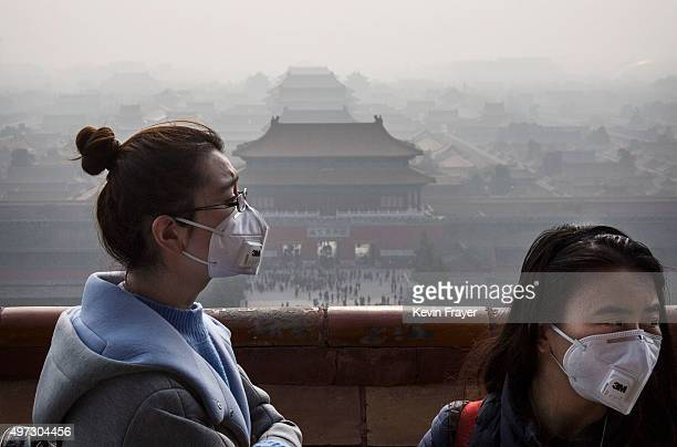 Chinese women wear masks as haze from smog caused by air pollution hangs over the Forbidden City on November 15 2015 in Beijing China As a result of...