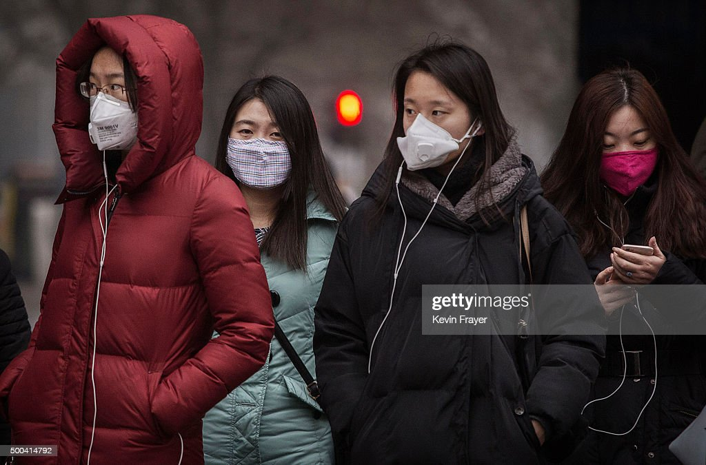 Chinese women wear masks to protect against pollution as they wait to cross the street in heavy smog on December 8 2015 in Beijing China The Beijing...