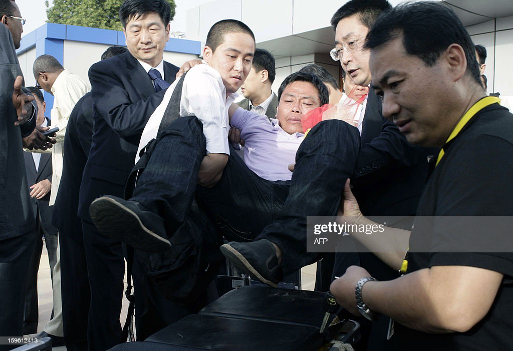 A Chinese worker (C) abducted by Darfur rebels earlier this month, is carried away on a stretcher upon his arrival at the Khartoum airport after his release on January 17, 2013. Four Chinese workers abducted by Darfur rebels on January 12 have been freed, a spokeswoman for the joint UN-African Union peace keeping force in the troubled western Sudan region. AFP PHOTO / EBRAHIM HAMID