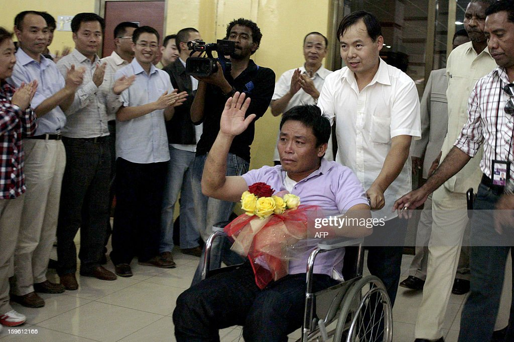 A Chinese worker (C) abducted by Darfur rebels earlier this month, waves on his wheelchair upon his arrival at the Khartoum airport after his release on January 17, 2013. Four Chinese workers abducted by Darfur rebels on January 12 have been freed, a spokeswoman for the joint UN-African Union peace keeping force in the troubled western Sudan region.