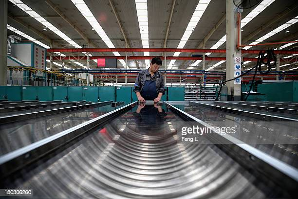 Chinese worker assembles the elevator door at Brilliant elevator manufacture workshop of Yuanda Group Co Ltd on September 9 2013 in Shenyang of...