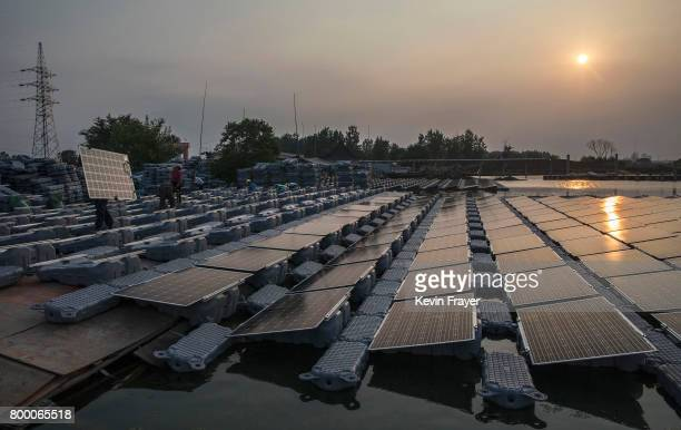 Chinese worker carries a panel that are part of a large floating solar farm project under construction by the Sungrow Power Supply Company on a lake...