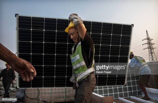 Chinese worker carries a panel that will be part of a large floating solar farm project under construction by the Sungrow Power Supply Company on a...