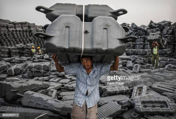 Chinese worker carries flotation devices used to support panels to be used in a large floating solar farm project under construction by the Sungrow...