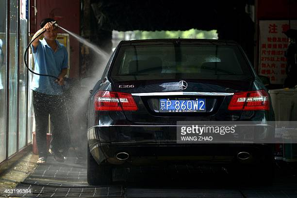 A Chinese worker cleans a Mercedes Benz at a car wash in Beijing on August 5 2014 German car company Daimler said on August 5 it was helping Chinese...