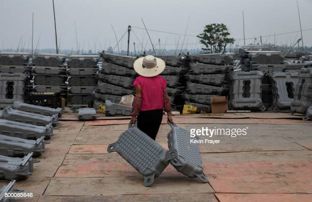 Chinese worker drags flotation devices to be used to support panels in a large floating solar farm project under construction by the Sungrow Power...