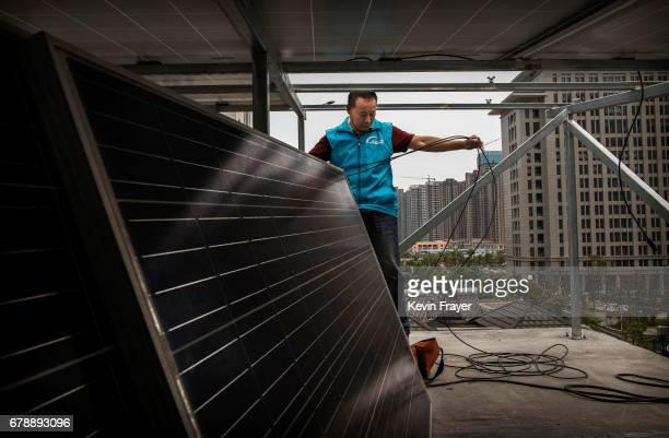 Chinese worker from Wuhan Guangsheng Photovoltaic Company fixes cables as he installs solar panels on the roof of a building on April 27 2017 in...