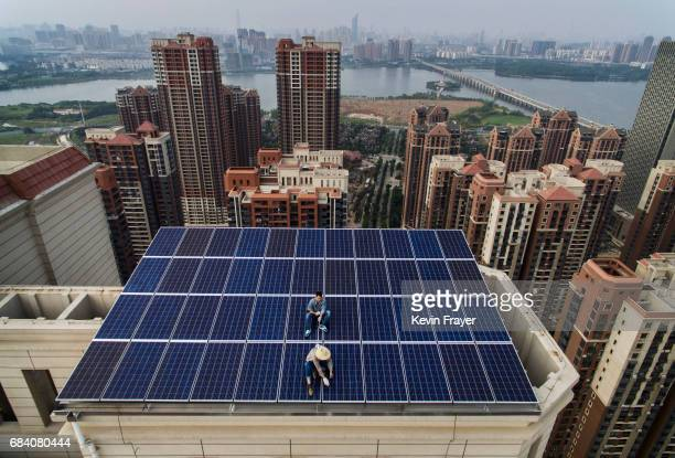 Chinese worker from Wuhan Guangsheng Photovoltaic Company holds a short rope to secure another as they finish a solar panel project on the roof of a...