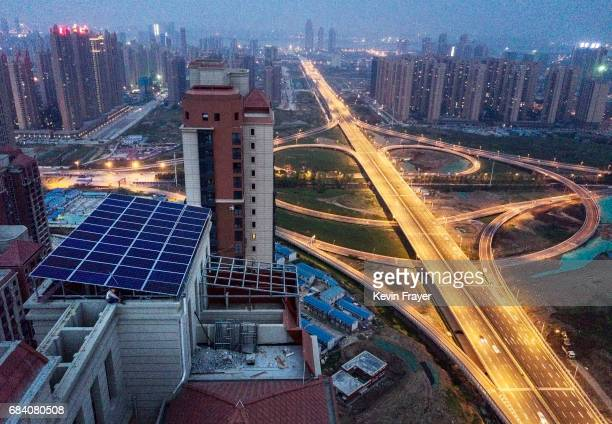 Chinese worker from Wuhan Guangsheng Photovoltaic Company rests after working on a solar panel project on the roof of a 47 story building in a new...
