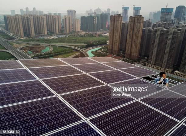 Chinese worker from Wuhan Guangsheng Photovoltaic Company talks on his phone as he works on a solar panel project on the roof of a 47 story building...