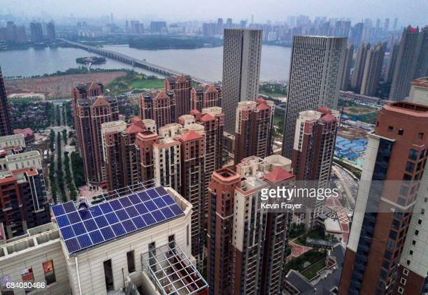 Chinese worker from Wuhan Guangsheng Photovoltaic Company works on a solar panel project on the roof of a 47 story building in a new development on...