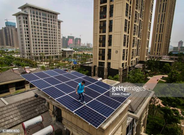 Chinese worker from Wuhan Guangsheng Photovoltaic Company works while installing a solar panel project on the roof of a building on April 27 2017 in...