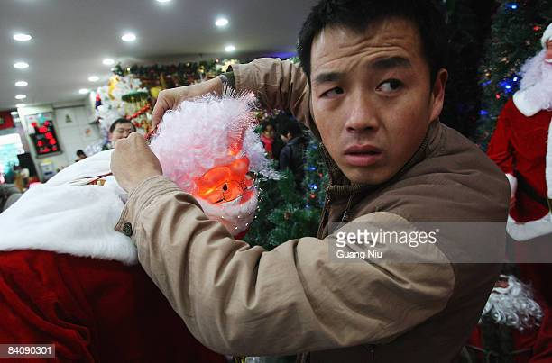 Chinese worker of a Christmas decorations store installs a model of Santa Claus at a market on December 19 2008 in Beijing China A large number of...