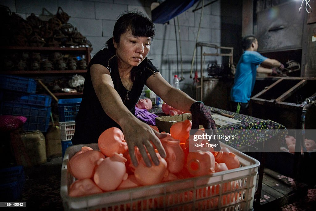 Chinese worker organizes plastic doll heads after they were made in an oven at a toy factory on September 17 2015 in Xietang Zhejiang Province China...