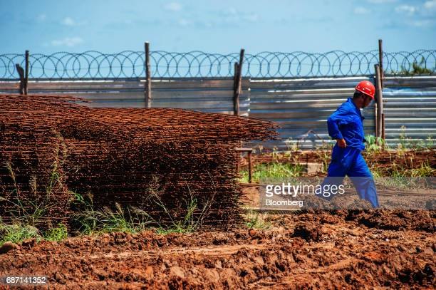 A Chinese worker passes steel reinforcement rods at the construction site for a hydro pumping station which will supply water from the Limpopo river...