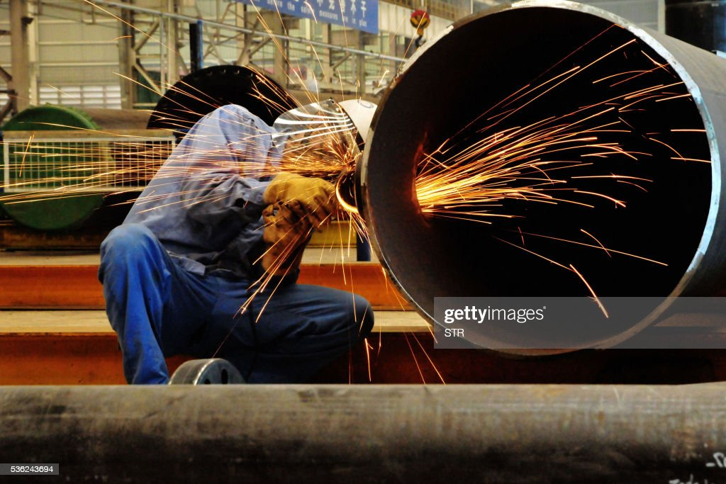 A Chinese worker polishes steel at an offshore oil engineering platform in Qingdao, east China's Shandong province on June 1, 2016. Activity in Chinese factories expanded for the third straight month in May, official data showed, a further sign of stabilisation in the world's second largest economy. / AFP / STR / China OUT