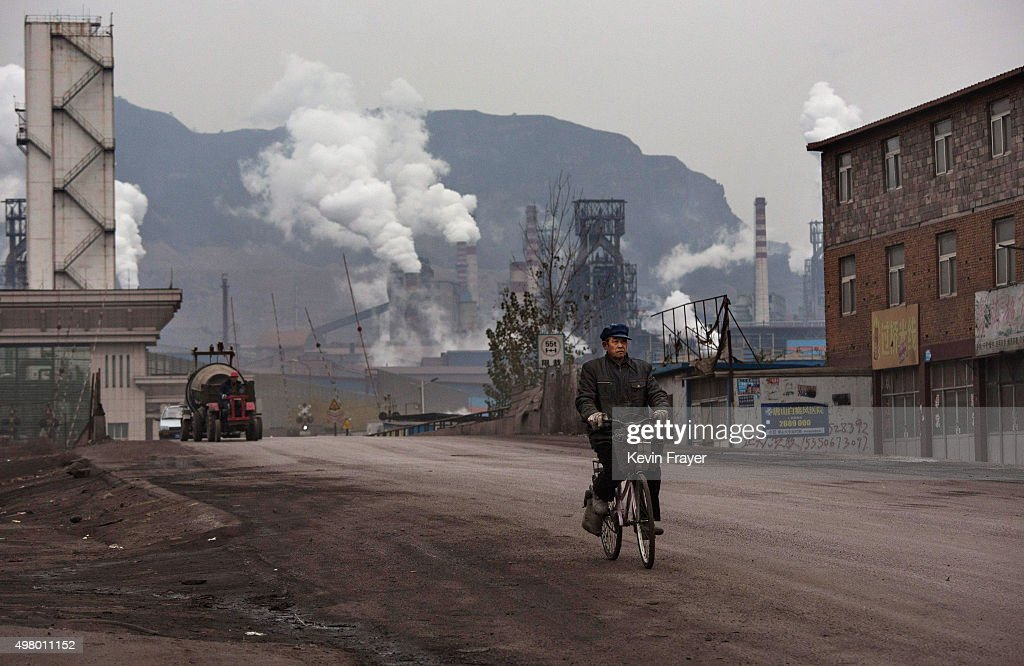 Chinese worker rides his bike as smoke billows from smokestacks at a steel factory on November 19 2015 in the industrial province of Hebei China...