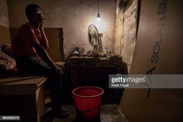 Chinese worker smokes in his quarters after working at the site of a large floating solar farm project under construction by the Sungrow Power Supply...