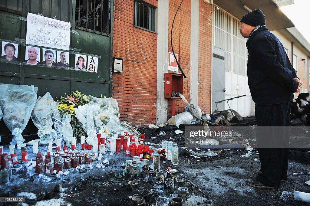 A Chinese worker stands at a memorial outside a clothing factory where seven Chinese workers were burned to death on December 4, 2013 in Prato, Italy. Seven people died and three were injured December 1, when a Chinese clothing factory in the industrial district of the Italian town of Prato in Tuscany burned, killing the workers trapped in a factory dormitory, where workers sleep, eat, and work.