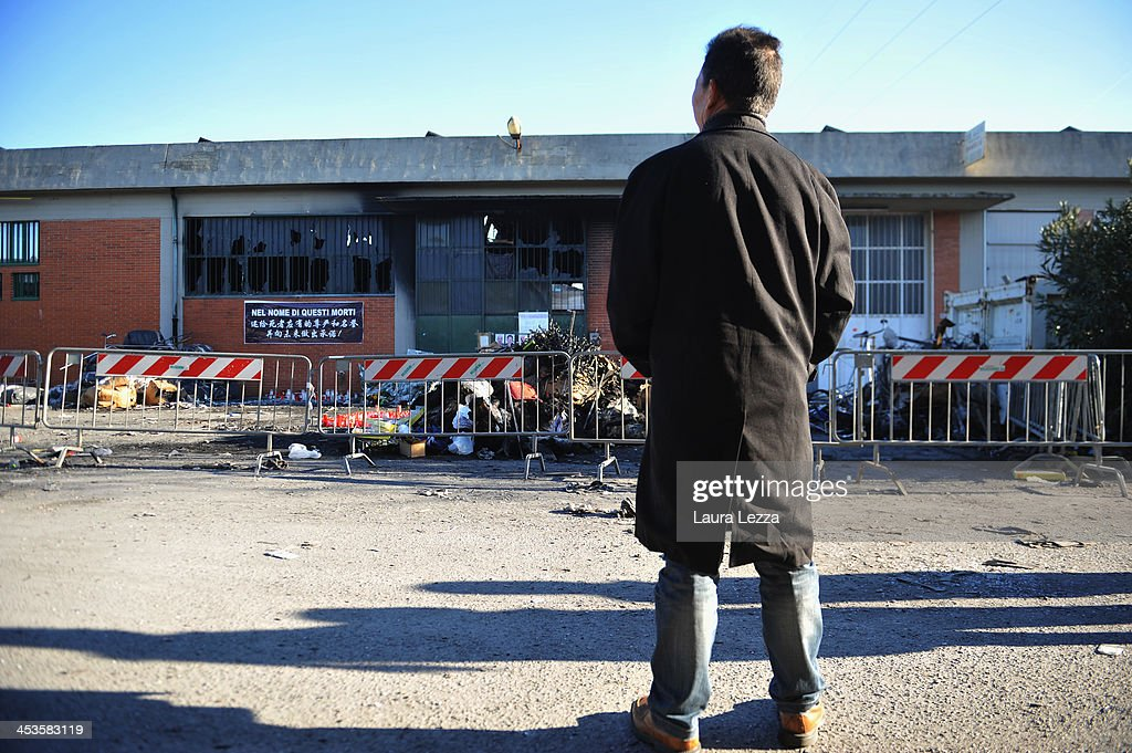 A Chinese worker stands outside a clothing factory where seven Chinese workers were burned to death on December 4, 2013 in Prato, Italy. Seven people died and three were injured December 1, when a Chinese clothing factory in the industrial district of the Italian town of Prato in Tuscany burned, killing the workers trapped in a factory dormitory, where workers sleep, eat, and work.
