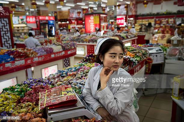Chinese worker waits for customers at a grocery store on January 20 2015 in central Beijing China China's economic growth slowed to its weakest point...