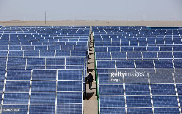Chinese worker walks in the solar modules of a newly installed 100MW photovoltaic ongrid power project on July 21 2010 in Dunhuang of China's...