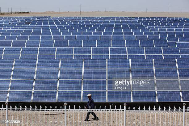 Chinese worker walks near the solar modules of a newly installed 100MW photovoltaic ongrid power project on July 21 2010 in Dunhuang of China's...