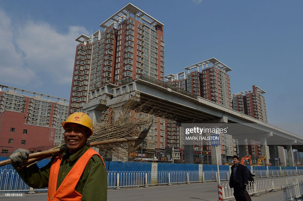 A Chinese worker walks past a new property development in Beijing on April 1, 2013. Chinese home prices picked up in March as buyers rushed to beat new government policies aimed at cracking down on speculation. China issued new rules in March to rein in prices, including a nationwide capital gains tax of 20 percent on profits owners make from selling residential property. AFP PHOTO/Mark RALSTON