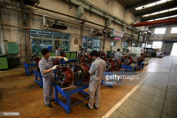 Chinese workers assemble the refrigeration compressors at China's largest refrigeration industrial enterprises Dalian Bingshan Group Co Ltd on...