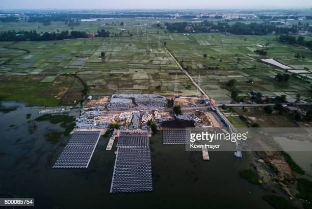Chinese workers build sections of a large floating solar farm project under construction by the Sungrow Power Supply Company on a lake caused by a...