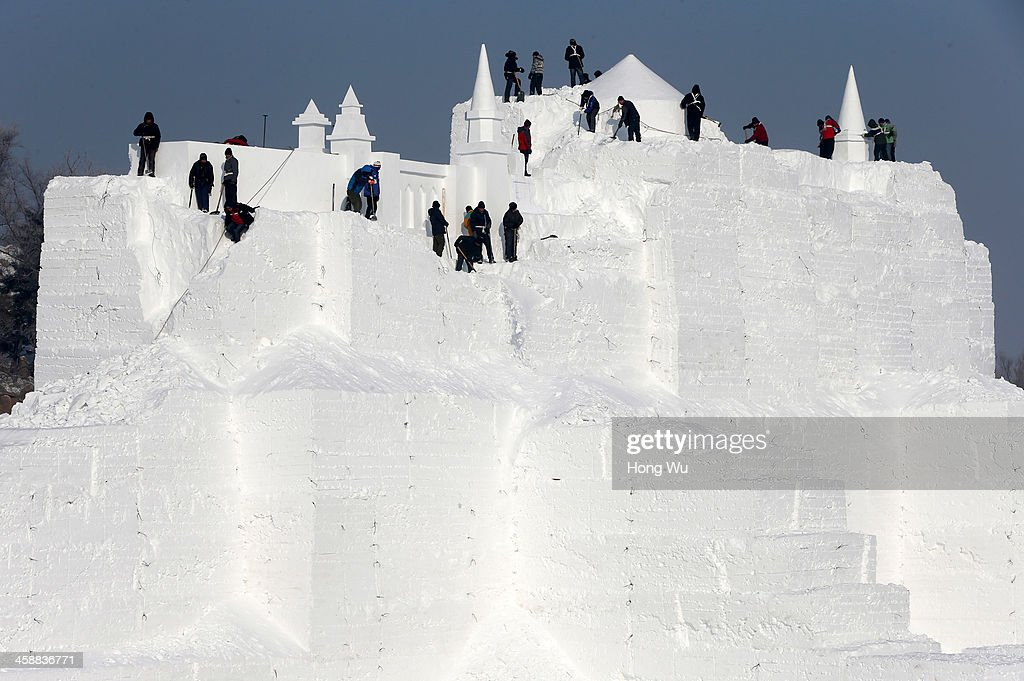 Chinese workers carve a large castle snow sculpture at the 26th Harbin International Snow Sculpture Art Expo in Sun Island park on December 22, 2013 in Harbin, China. The Harbin International Ice and Snow Sculpture Festival is one of the largest ice and snow festivals in the world and is a popular winter destination for both Chinese and foreign visitors.