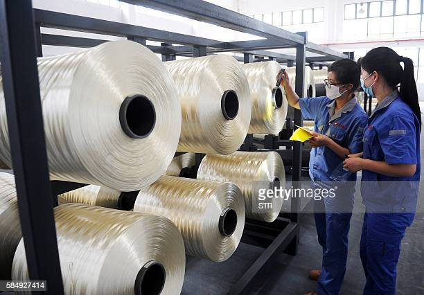 Chinese workers check carbon fiber silk thread at a carbon fiber factory in Lianyungang in eastern China's Jiangsu province on August 1 2016 China's...