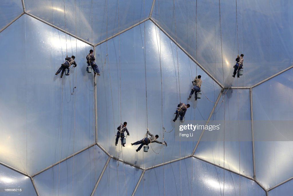 Chinese workers clean the bubble shaped surface of the National Aquatics Center, known as the Water Cube, on April 14, 2013 in Beijing, China. The Aquatics Center hosted the swimming, diving and Synchronized Swimming events during Beijing Olympic Games.