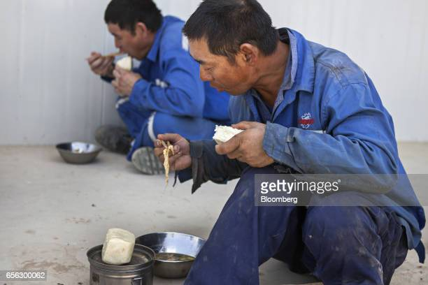 Chinese workers eat during a break at the Sindh Engro Coal Mining Co site in the Thar desert Pakistan on Thursday March 9 2017 In the dusty scrub of...