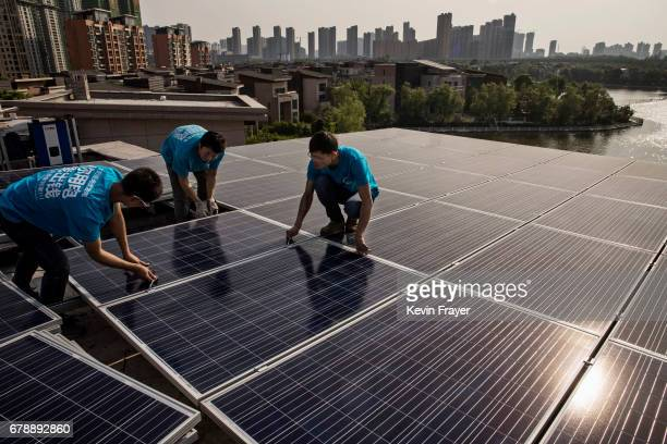 Chinese workers from Wuhan Guangsheng Photovoltaic Company install solar panels on the roof of a building on April 27 2017 in Wuhan ChinaAs the...