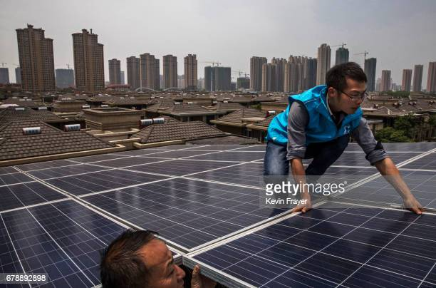 Chinese workers from Wuhan Guangsheng Photovoltaic Company install solar panels on the roof of a building on April 27 2017 in Wuhan China As the...
